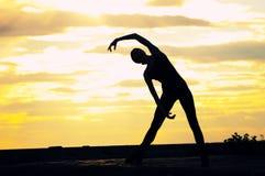 Silhouette de femme de danse au-dessus de coucher du soleil. Yoga Images stock