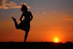 Silhouette de femme de danse sur le coucher du soleil Images stock
