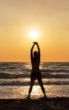 Silhouette de femme faisant des étendues sur la plage Images stock