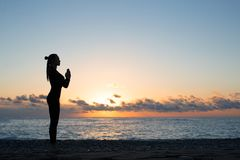 Silhouette de femme faisant la salutation au soleil sur la plage au lever de soleil, yoga de matin photo libre de droits