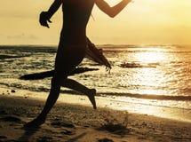 Silhouette de femme fonctionnant le long du rivage de l'océan Photographie stock libre de droits