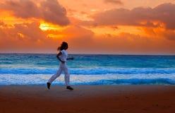Silhouette de femme, fonctionnant sur le coucher du soleil le long de l'océan Photographie stock
