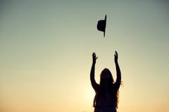 Silhouette de femme jetant son chapeau dans le ciel Photo libre de droits