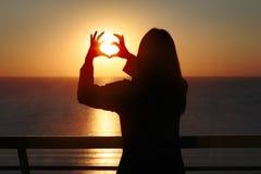 Silhouette de femme montrant le geste de main de coeur d'amour dans le lever de soleil de matin Image stock