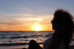 Silhouette de femme observant un coucher du soleil dans Ibiza Image stock
