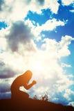Silhouette de femme priant au-dessus du beau fond de lever de soleil Photo stock