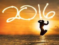 Silhouette de femme sautant sous les numéros 2016 Image stock