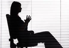 Silhouette de femme se reposant dans le bureau (abat-jour) Images libres de droits