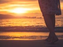 Silhouette de femme seul marchant sur la plage pendant le coucher du soleil Image stock