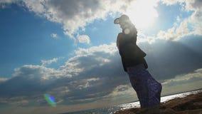 Silhouette de femme seule se tenant sur le bord de la mer au soleil, relations cassées banque de vidéos