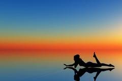 Silhouette de femme sur bleu et orange Image stock
