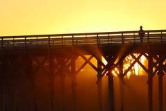 Silhouette de femme sur le pilier au coucher du soleil Images libres de droits