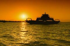 Silhouette de ferry-boat contre le coucher du soleil Photographie stock