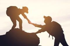 Silhouette de fille aidant un garçon sur la montagne supérieure Photos libres de droits