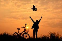 Silhouette de fille avec la bicyclette Photos stock
