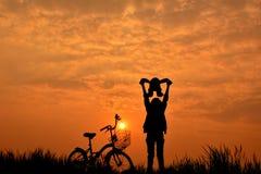 Silhouette de fille avec la bicyclette sur l'herbe Photos libres de droits