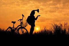 Silhouette de fille avec la bicyclette sur le champ d'herbe Image stock