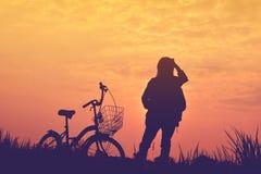 Silhouette de fille avec la bicyclette sur le champ d'herbe Images stock