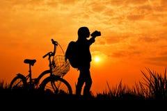 Silhouette de fille avec la bicyclette sur le champ d'herbe Photos libres de droits