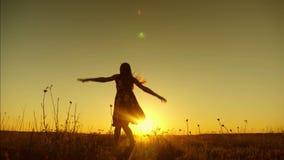 Silhouette de fille avec de longs cheveux en désordre sautant en vol dans la lumière lumineuse du coucher de soleil Femme libre e clips vidéos