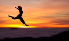 Silhouette de fille branchant dans le coucher du soleil Images libres de droits