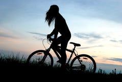 Silhouette de fille de cycliste de montagne Photographie stock libre de droits
