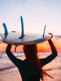 Silhouette de fille mince dans le wetsuit avec de longs cheveux et planche de surf sur la plage au coucher du soleil ou au lever  Image libre de droits