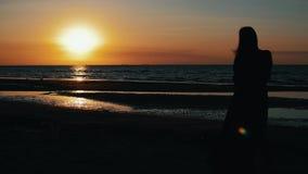 Silhouette de fille posant au photographe sur la plage sur le coucher du soleil Mer Photoshoot clips vidéos