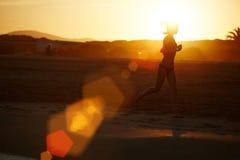 Silhouette de fille sportive fonctionnant le long de la plage sur le fond orange étonnant de coucher du soleil Photographie stock libre de droits