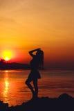 Silhouette de fille sur le fond de plage de coucher du soleil Photographie stock libre de droits