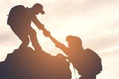 Silhouette de garçon aidant une fille sur la montagne supérieure Images libres de droits
