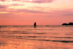 Silhouette de garçon seul marchant sur la plage tropicale Photographie stock libre de droits