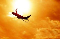 Silhouette d'avion sur le fond de coucher du soleil Photos libres de droits