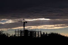 Silhouette de grue de construction dans les nuages images libres de droits