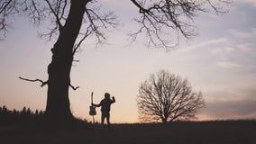 Silhouette de guitariste au mouvement lent de coucher du soleil courses avec une guitare dans des ses mains banque de vidéos