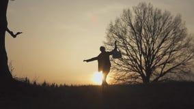 Silhouette de guitariste au mouvement lent de coucher du soleil ondulation de sa guitare et main banque de vidéos