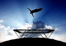 Gymnaste sur le trempoline dans le coucher du soleil Photo stock