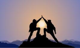 Silhouette de 2 hommes, dessus de montagne, coucher du soleil Images stock