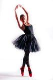 Silhouette de jeune ballerine posant dans des chaussures blanches de tutu et de ballet sur le fond blanc Images stock