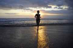 Silhouette de jeune femme asiatique sexy heureuse dans le fonctionnement de bikini excité sur la plage de coucher du soleil Image stock