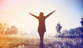 Silhouette de jeune femme avec les mains ouvertes Photo stock