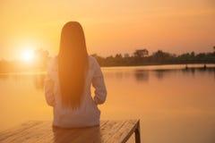 Silhouette de jeune femme de détente sur le pilier en bois au lac dans le coucher du soleil Photographie stock libre de droits