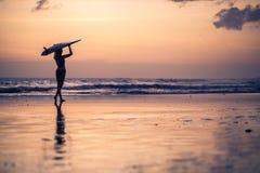 Silhouette de jeune femme marchant le long de la plage au coucher du soleil Photos libres de droits