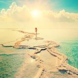 Silhouette de jeune femme marchant sur la mer morte Photos stock