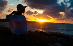 Silhouette de jeune femme par l'océan au coucher du soleil photographie stock