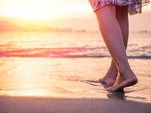 Silhouette de jeune femme seul marchant sur la plage dans le coucher du soleil Image stock