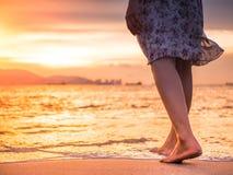 Silhouette de jeune femme seul marchant sur la plage dans le coucher du soleil Image libre de droits