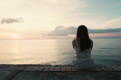 Silhouette de jeune femme seul se reposant de l'arrière extérieur à photo libre de droits