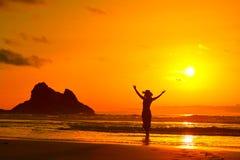 Silhouette de jeune femme sur la plage dans le coucher du soleil d'été Photo libre de droits
