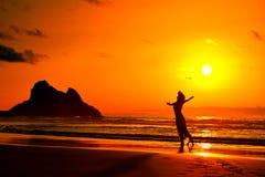 Silhouette de jeune femme sur la plage dans le coucher du soleil d'été Photographie stock libre de droits